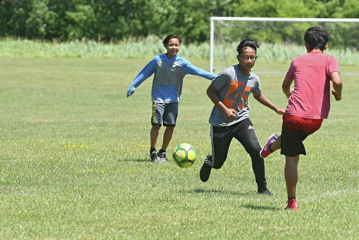 Klue Thaw, 13, left, Bae Reh, 14, and Sakler Moo, 14, practice with some of their soccer team. (Lori Van Buren/Times Union)