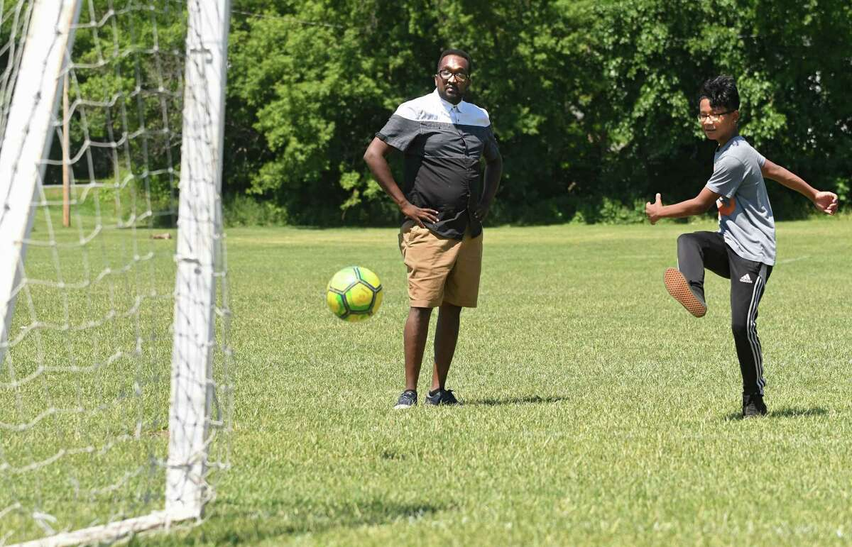 Coach Amjad Abdalla watches Bae Reh, 14, kick the ball as they practices with their some of their soccer team. (Lori Van Buren/Times Union)