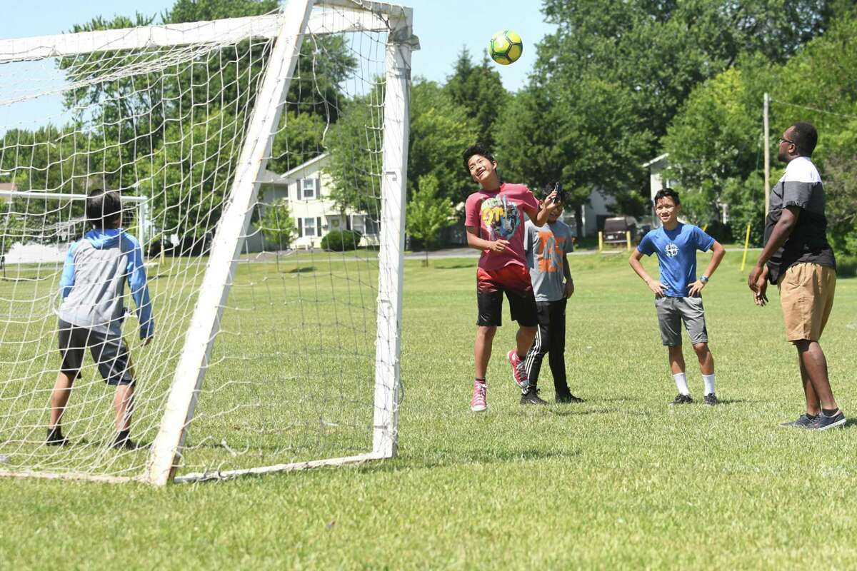 From left, Klue Thaw, 13, Sakler Moo, 14, Bae Rey, 14, Eh Thay, 14, and Coach Amjad Abdalla watches Bae Reh, 14, practice with some of their soccer team at Hoffman Park. (Lori Van Buren/Times Union)