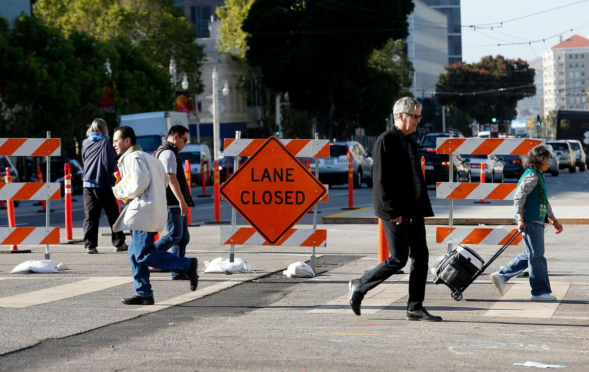 Pedestrians cross Van Ness Avenue at McAllister Street where construction work continues on express bus lanes in San Francisco, Calif. on Friday, June 29, 2018.
