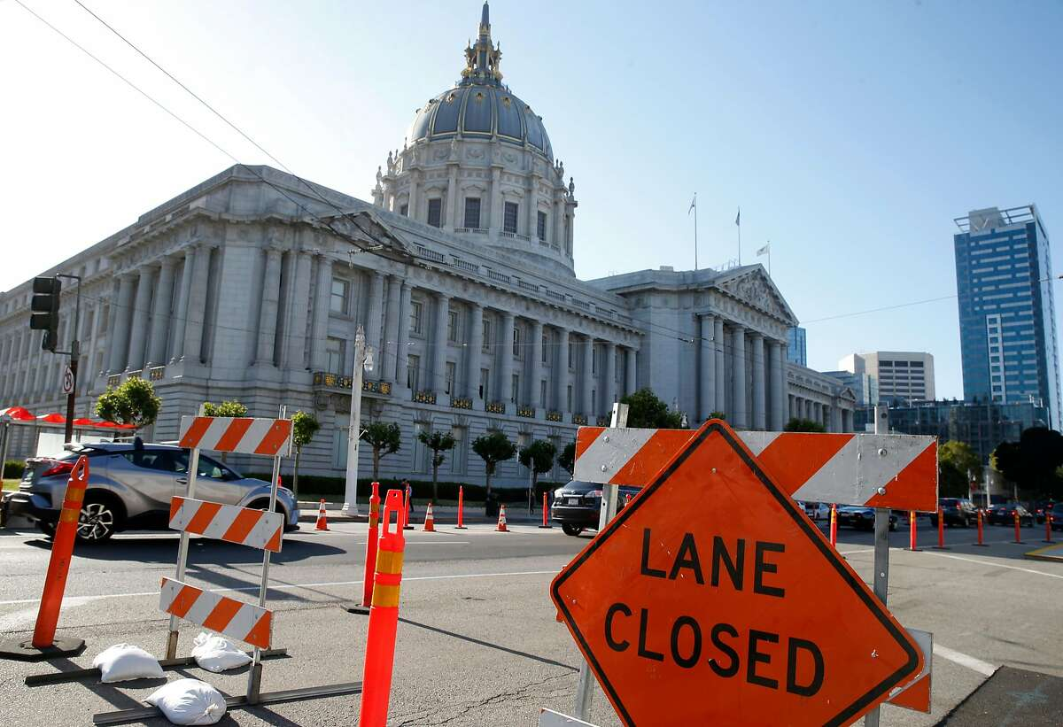 Traffic is rerouted through a construction zone in front of City Hall as work on express bus lanes continues on Van Ness Avenue in San Francisco, Calif. on Friday, June 29, 2018.