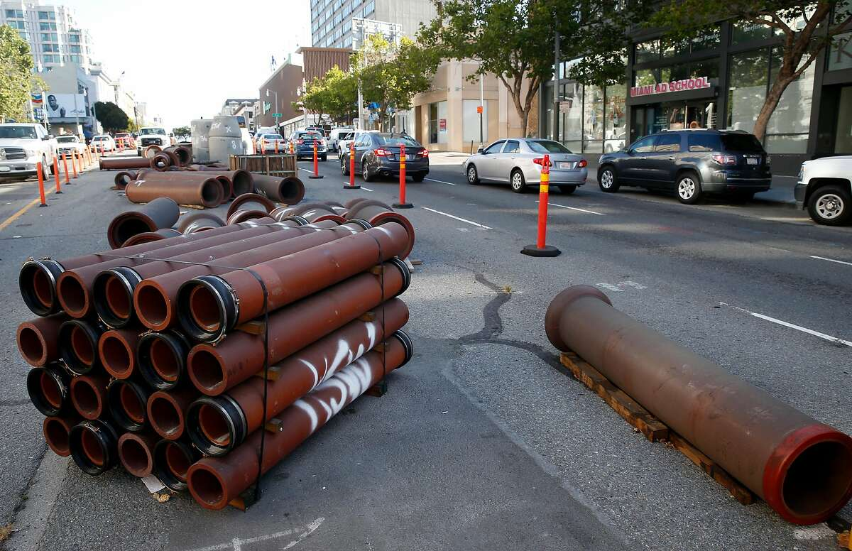 Sections of underground pipe are stored in the center divider as construction continues on express bus lanes on Van Ness Avenue in San Francisco, Calif. on Friday, June 29, 2018.