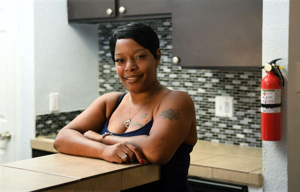 Latasha Murchison beams in the dining room of her new home that she moved into with the help of the disaster relief agency NAM on June 28, 2018. (Jerry Baker/For the Chronicle)