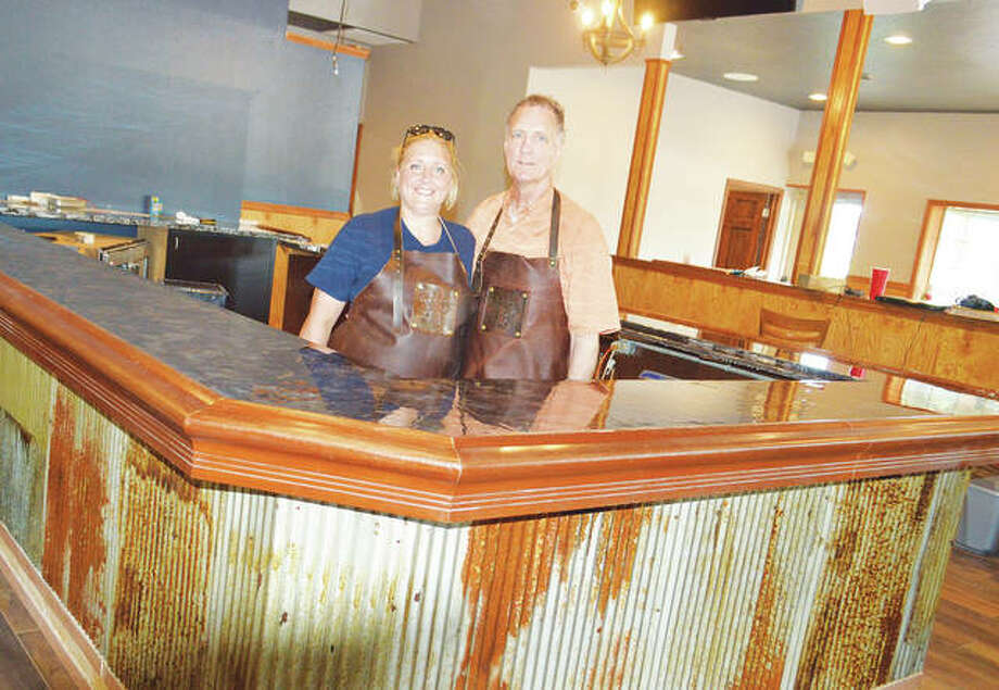 Kelsi Baker Walden and Rex Hale stand behind the new Bakers & Hale restaurant's bar, which is wrapped in corrugated tin from an old barn. The restaurant will open sometime in July. Photo:     Vicki Bennington|For The Telegraph