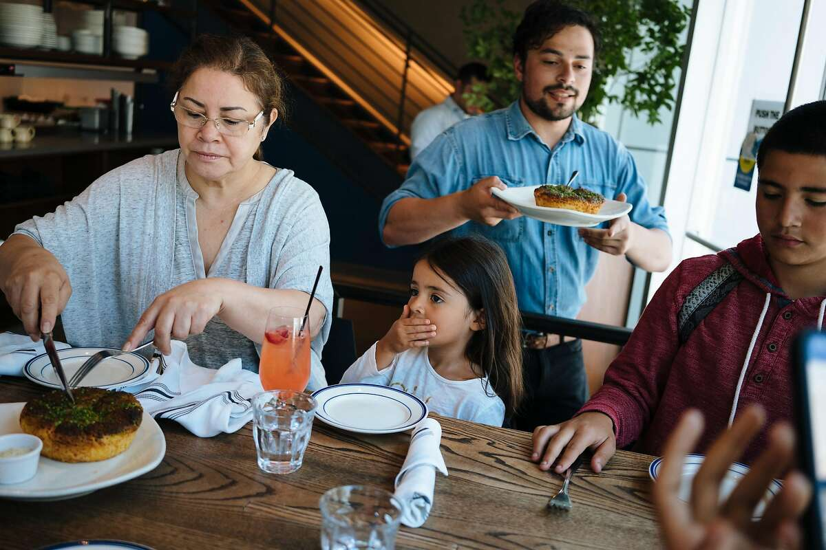 Maria Becerra prepress to cut up a dish for Yazmin Becerra, 4, during the family's lunch at the Corridor in San Francisco, Calif., on Friday, June 29, 2018.