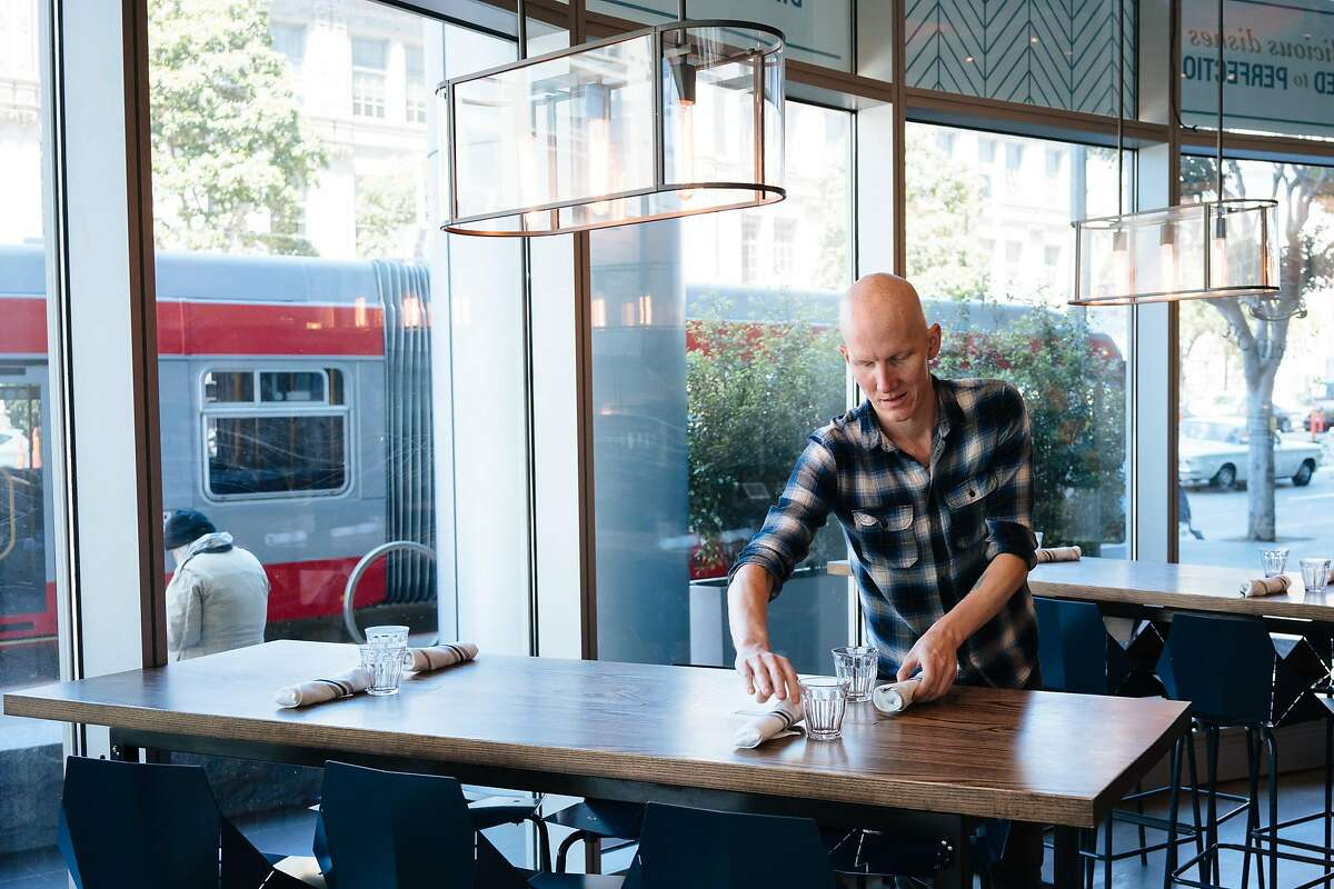 Andrew Worley sets the table before the lunch rush at the Corridor in San Francisco, Calif., on Friday, June 29, 2018.