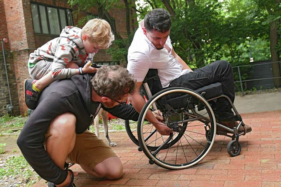Aimal, a former Afghan translator who worked with US troops, shows his neighbor Jim Maximowicz a broken part of his wheelchair upon returning home from work on Wednesday, June 27, 2018 in Albany, N.Y. Riley Maximowicz, 5, sits on his dad's back. Aimal was shot in the spine while saving a US Marine from an ambush. His Marine buddies have set up a GoFundMe page to replace his broken wheelchair. (Lori Van Buren/Times Union) Photo: Lori Van Buren, Albany Times Union / 20044205A