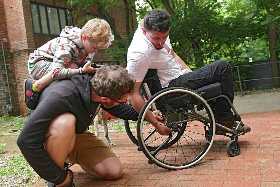 Aimal, a former Afghan translator who worked with US troops, shows his neighbor Jim Maximowicz a broken part of his wheelchair upon returning home from work on Wednesday, June 27, 2018 in Albany, N.Y. Riley Maximowicz, 5, sits on his dad's back. Aimal was shot in the spine while saving a US Marine from an ambush. His Marine buddies have set up a GoFundMe page to replace his broken wheelchair. (Lori Van Buren/Times Union)