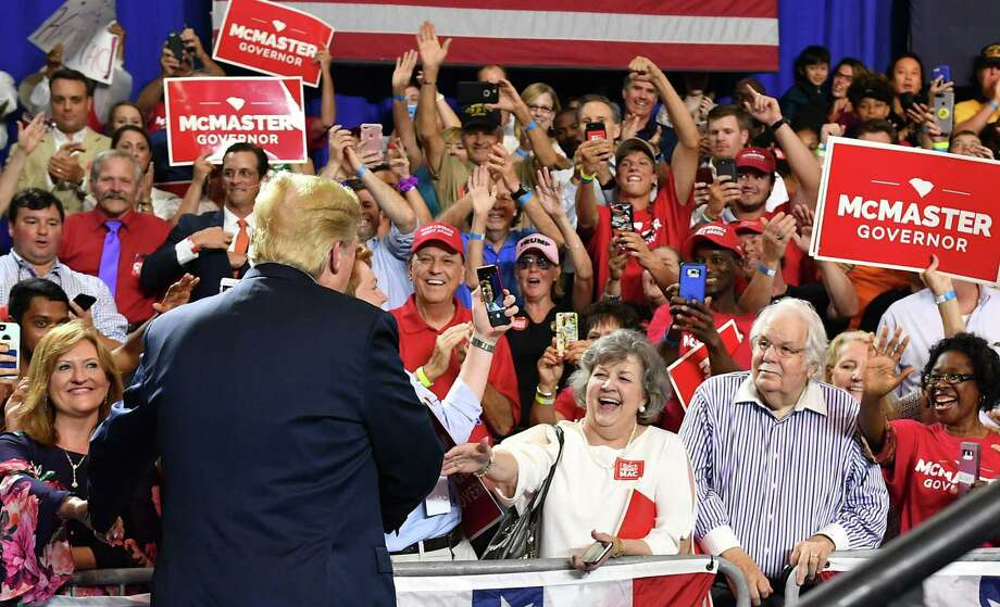 """President Donald Trump greets supporters as he arrives to speak at a rally for South Carolina Governor Henry McMaster at Airport High School in West Columbia, South Carolina on Monday. On immigration, his supporters stick with him because they don't like the """"catch-and-release"""" process that he tried to change. Photo: MANDEL NGAN /AFP /Getty Images / AFP or licensors"""