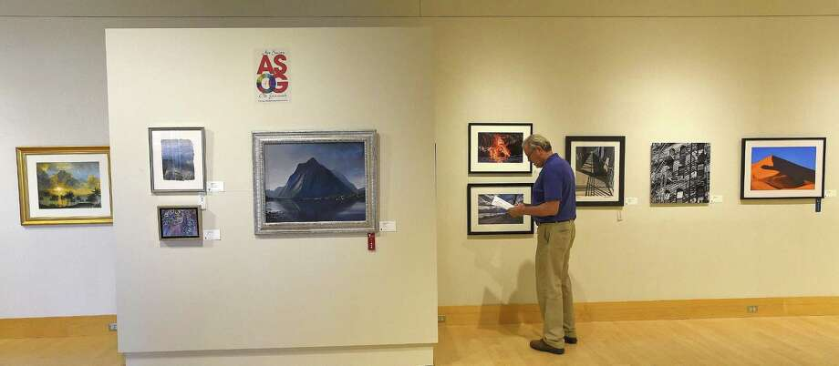 "A visitor to the Flinn Art Gallery takes in the Art Society of Old Greenwich art exhibit entitled ""Escape"" display at the Greenwich Library on June 29, 2018 in Greenwich, Connecticut. Photo: Matthew Brown / Hearst Connecticut Media / Stamford Advocate"