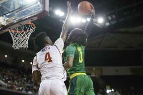 Oregon's Dwayne Benjamin dunks the ball over Southern California's Chimezie Metu, left, during the first half of an NCAA college basketball game, Saturday, March 5, 2016, in Los Angeles. (AP Photo/Danny Moloshok)
