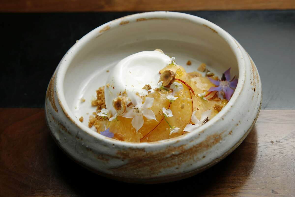 The frozen yogurt with peach, hazelnut and coconut caramel at Sorrel, Tuesday, June 19, 2018, in San Francisco, Calif.