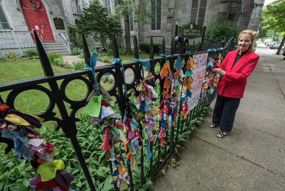 Pastor Judith Johnson-Siebold stands by the fence at the front of her church, The Christ Church United Methodist and the ribbon project which are a symbol of solidarity with the 2,300 children separated from their families at the Mexican border Wednesday June 27, 2018 in Troy, N.Y. (Skip Dickstein/Times Union) Photo: SKIP DICKSTEIN / 20044206A