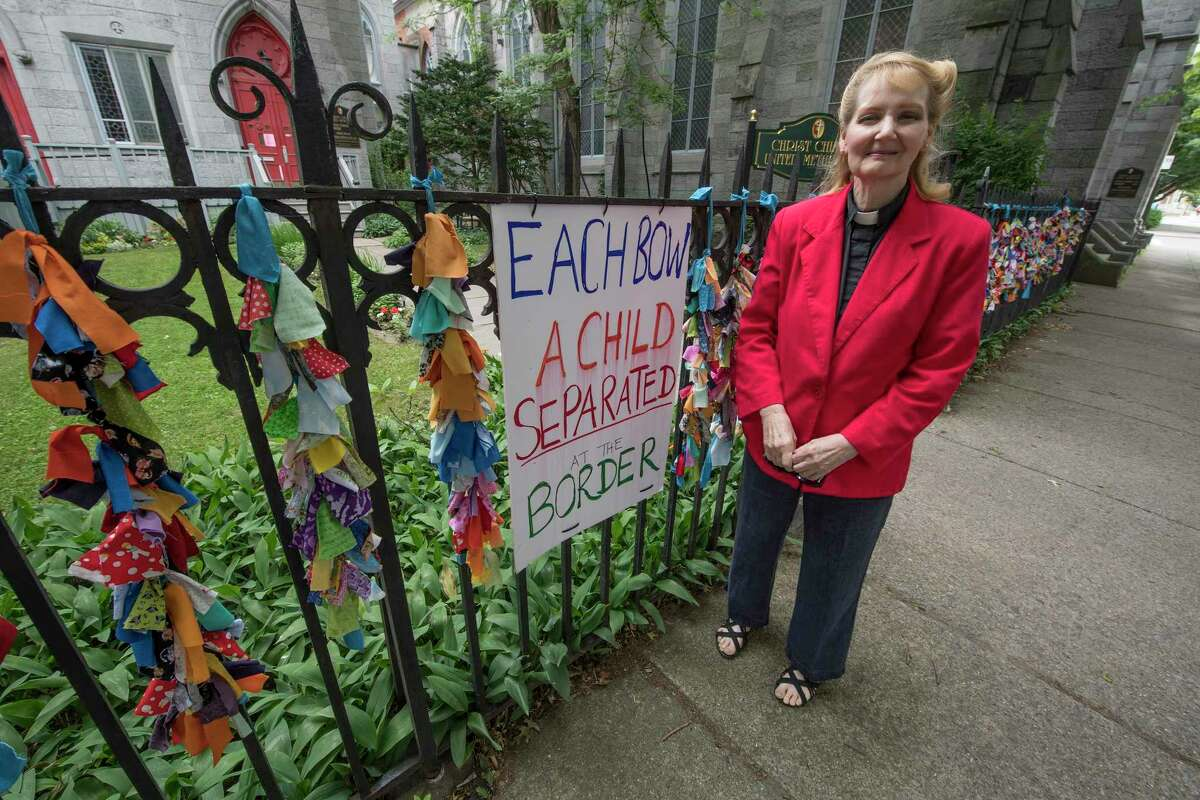 Pastor Judith Johnson-Siebold stands by the fence at the front of her church, The Christ Church United Methodist and the ribbon project which are a symbol of solidarity with the 2,300 children separated from their families at the Mexican border Wednesday June 27, 2018 in Troy, N.Y. (Skip Dickstein/Times Union)