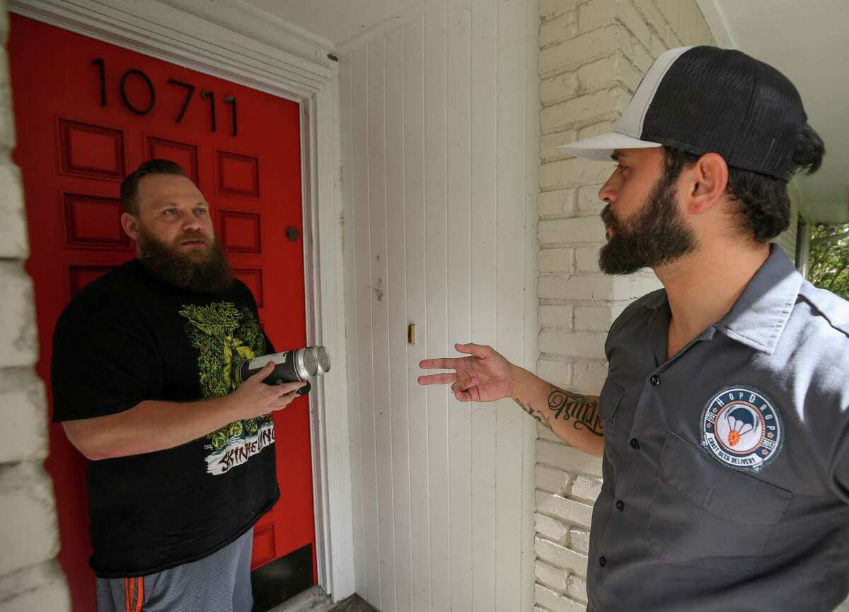 Ricardo Pardillo, right, who works with HopDrop, delivers beer to Graham Adams at his residence Friday, June 29, 2018, in Houston. HopDrop launched late last year to provide home delivery of local and hard-to-find beers. H-E-B and its delivery service Favor announced Friday that the grocer will now offer home delivery of beer and wine. ( Godofredo A. Vasquez / Houston Chronicle )