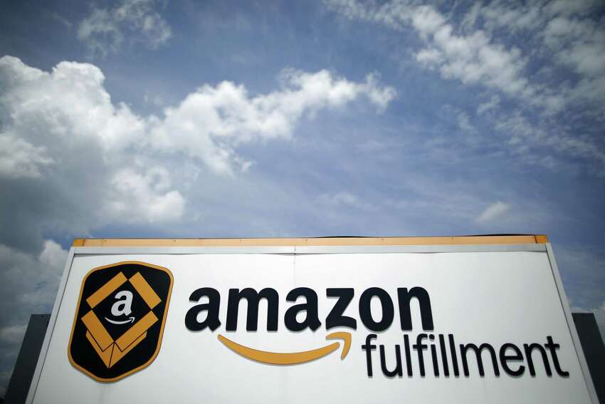 Signage is displayed outside the Amazon.com fulfillment center in Kenosha, Wisconsin, U.S., on Tuesday, Aug. 1, 2017. Amazon.com Inc. held a giant job fair at nearly a dozen U.S. warehouses as part of its effort to hire 100,000 people in the U.S. by 2018. Photographer: Jim Young/Bloomberg ORG XMIT: 775019410