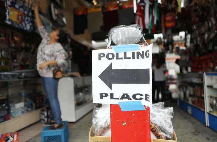 LOS ANGELES, CA - JUNE 05:  A woman hangs items for sale behind a sign pointing to the polling place at El Mercado de Los Angeles, in the Boyle Heights neighborhood, during the state's primary election on June 5, 2018 in Los Angeles, California. California could play a determining role in upsetting Republican control in the U.S. Congress, as Democrats hope to win 10 of the 14 seats held by Republicans.  (Photo by Mario Tama/Getty Images)