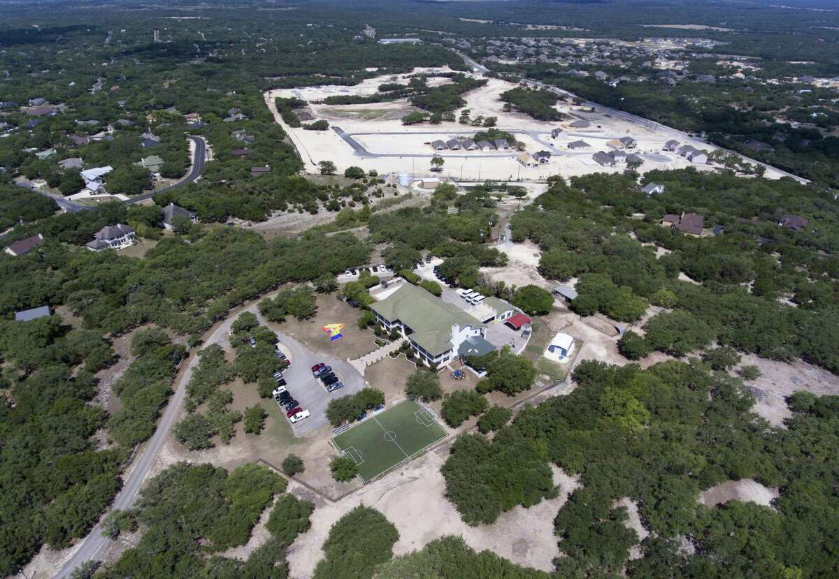 The Southwest Key Casa Blanca facility, foreground, operates out of a $1.5 million mansion in the Timberwood Park subdivision near San Antonio.