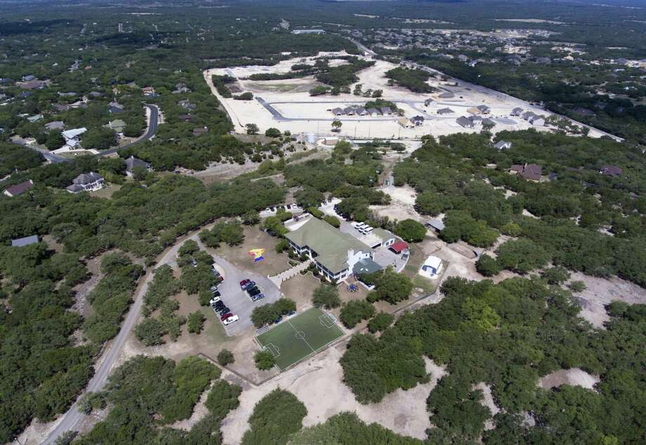The Southwest Key Casa Blanca facility, foreground, operates out of a $1.5 million mansion in the Timberwood Park subdivision near San Antonio. Photo: William Luther /San Antonio Express-News / © 2018 San Antonio Express-News