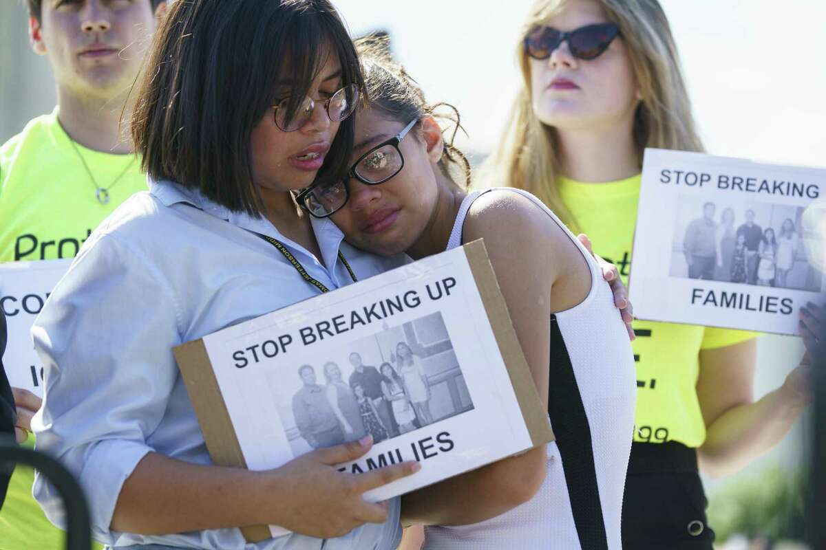 Nicole Edralin, 15, (left) comforts her sister Michelle Edralin, 12, both of Highland Park, N.J., as they protest outside the Supreme Court Building last week in Washington, D.C. Their father, Cloyd, is currently being detained by ICE.