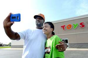 "J. J. Garrett and daughter Jamie, 10, take a photo together in front of the Beaumont Toys R Us store Friday. They had come to take a final trip through the store, but found it had had closed a day earlier than scheduled. After 70 years in business, Toys R Us stores across the nation closed their doors for the final time Friday, June 29. Garrett says he remembers the excitement when Toys R Us opened in Beaumont decades ago. ""There were no other toy stores,"" he says. ""One day it just popped up."" The store quickly became a part of the family's holiday tradition. ""We came every Christmas,"" he recalls. It was a tradition he maintained with his own family, including wife Pearlina and daughter Jamie. ""Christmas wouldn't be Christmas without the Toys R Us store. I'm going to really miss that."" He added that, in the era of convenience, one-stop shopping venues such as Walmart make it difficult for specialty stores that require a separate shopping trip to be sustainable. The added allure, convenience and often cheaper pricing of online shopping even further impacts a specialty brick and mortar store. The family was among those stopping outside the store, taking photos and reminiscing about childhood memories at the store. Friday, June 29, 2018 Kim Brent/The Enterprise"