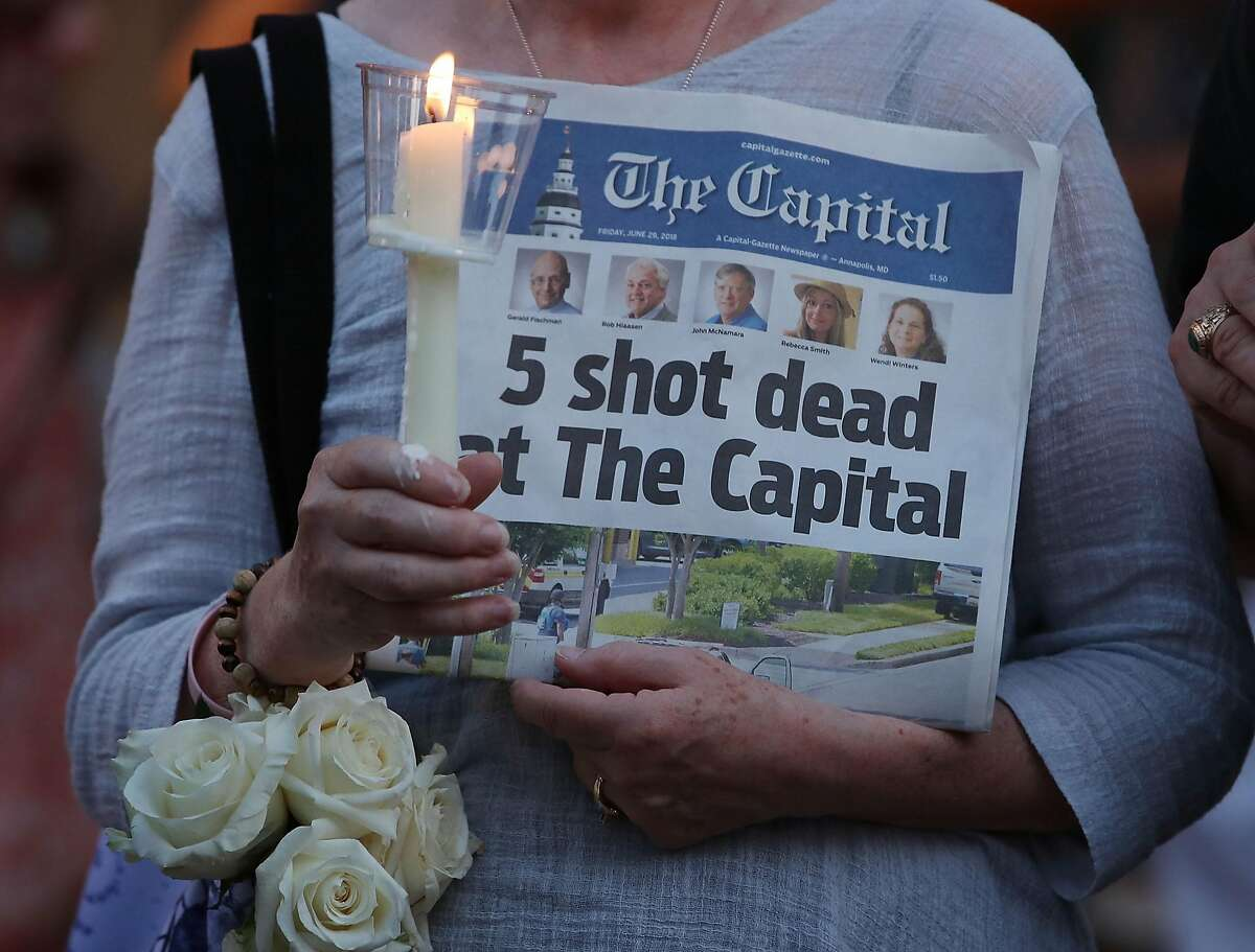 CAPITAL GAZETTE SHOOTING: A women holds a June 30, 2018, edition of the Capital Gazette newspaper during a candlelight vigil to honor the 5 people who were shot and killed a day earlier in Annapolis, Maryland. Jarrod Ramos of Laurel Md. has been arrested and charged with killing 5 people at the daily newspaper. He had been angered by an article about him.