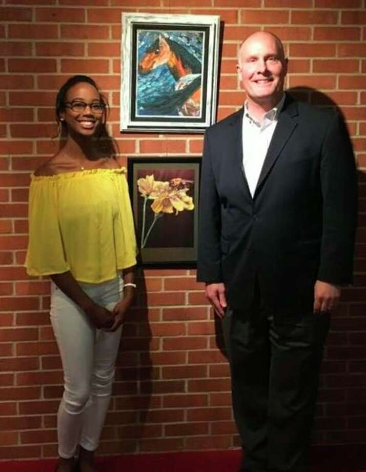 FILE — U.S. Rep. John Moolenaar congratulates Genesia Thompson on winning the Congressional Art Competition for Michigan's Fourth Congressional District during a presentation at the Midland Center for the Arts on May 2, 2018. Thompson's winning piece, 'October,' is in the center. It features marigolds and a bee.