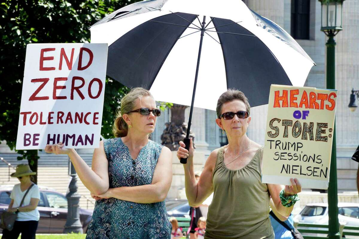 Camille Jobin-Davis, left, and Fran Gorka, both of Voorheesville, hold placards during the People for the American Way's nationwide day of protest against the Trump administration?•s treatment of immigrants at the Capitol Saturday June 30, 2018 in Albany, NY. (John Carl D'Annibale/Times Union)
