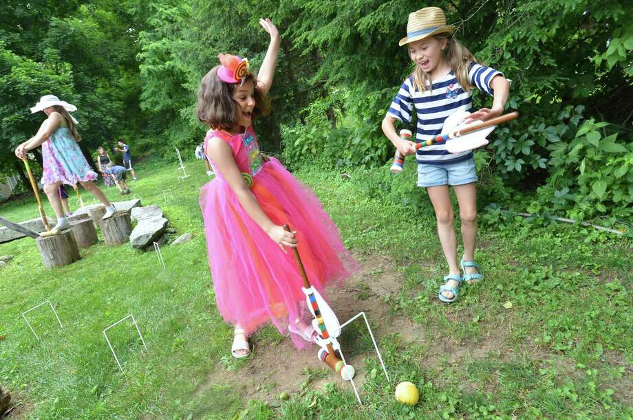 Sienna Criscuolo and Olivia Edwards cheer during a game of croquet at the Wilton Historical Society's Magical Mad Hatter Tea Party on Wednesday June 27, 2018 in Wilton Conn. Photo: Alex Von Kleydorff / Hearst Connecticut Media / Norwalk Hour