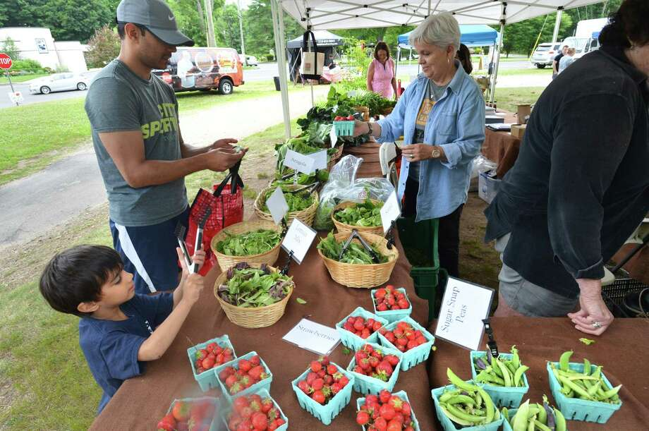 Niki Kohl and his son Daven buy some fresh strawberries at the Ambler Farm stand during Wilton Farmers Market at the Wilton Historical Society on Wednesday June 27, 2018 in Wilton Conn Photo: Alex Von Kleydorff / Hearst Connecticut Media / Norwalk Hour