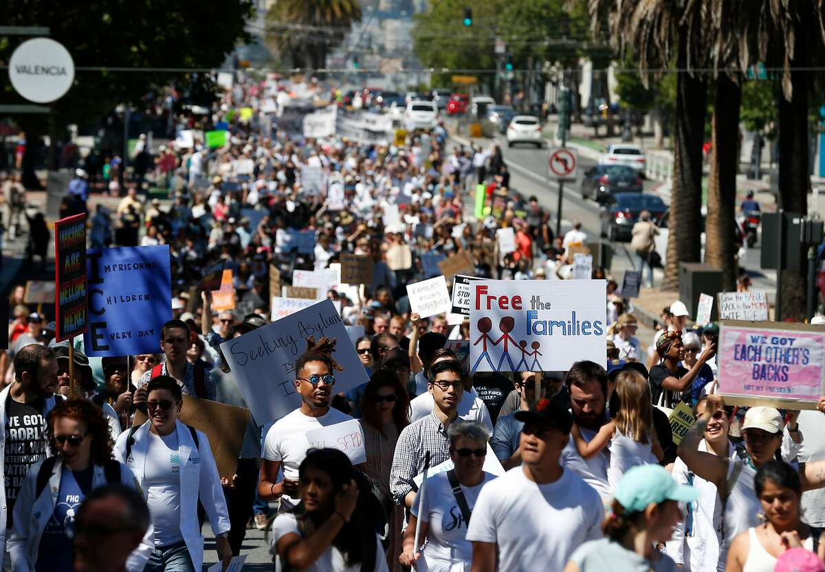 Thousands of people march along Market Street to San Francisco City Hall for a rally protesting President Trump's immigration policies.
