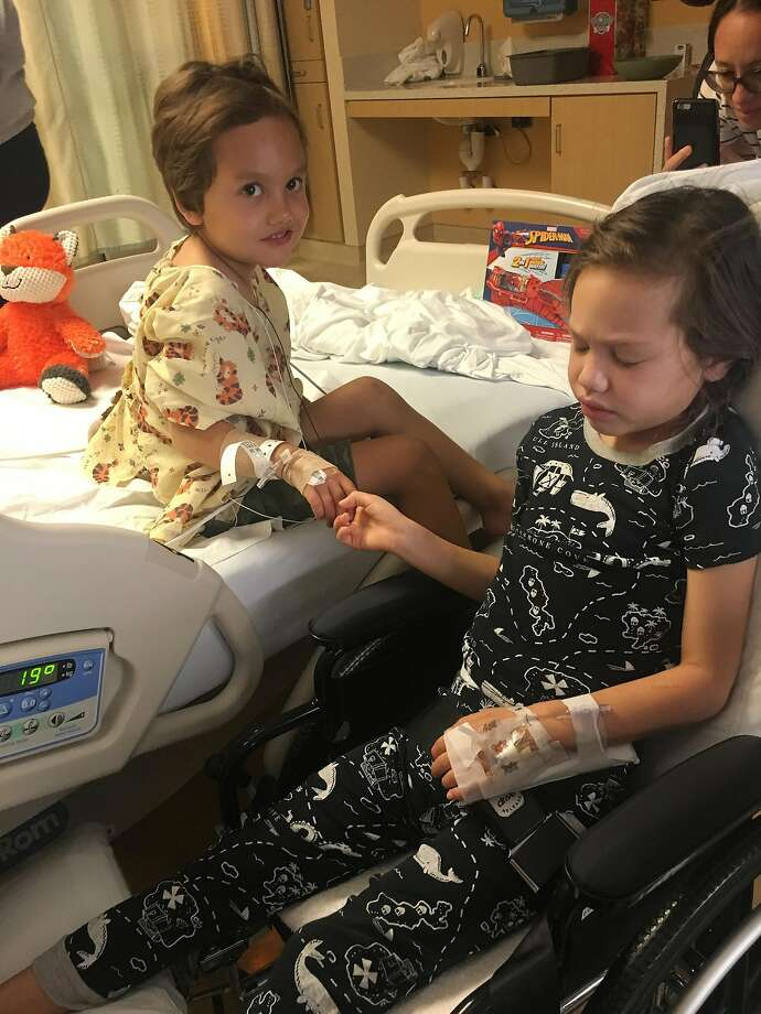 Four-year-old Noah Avery (left) holds hands with his sister, Kalea, 6, at the hospital in Long Beach. Photo: Courtesy Avery Family