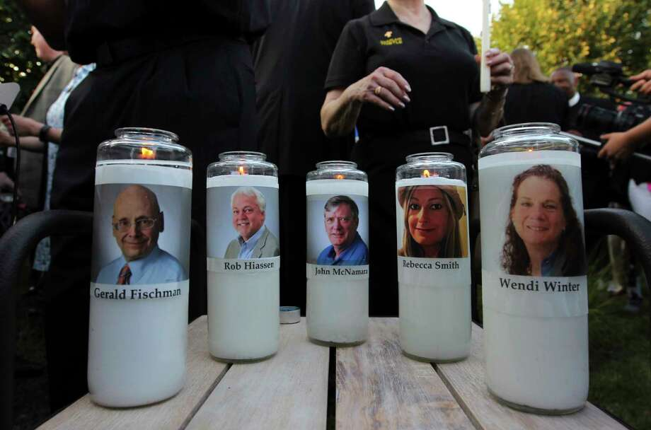 Photos of five journalists adorn candles during a vigil across the street from where they  were slain in their newsroom in Annapolis, Md., Friday, June 29, 2018. Prosecutors say Jarrod W. Ramos opened fire Thursday in the Capital Gazette newsroom. (AP Photo/Jose Luis Magana) Photo: Jose Luis Magana / Copyright 2018 The Associated Press. All rights reserved