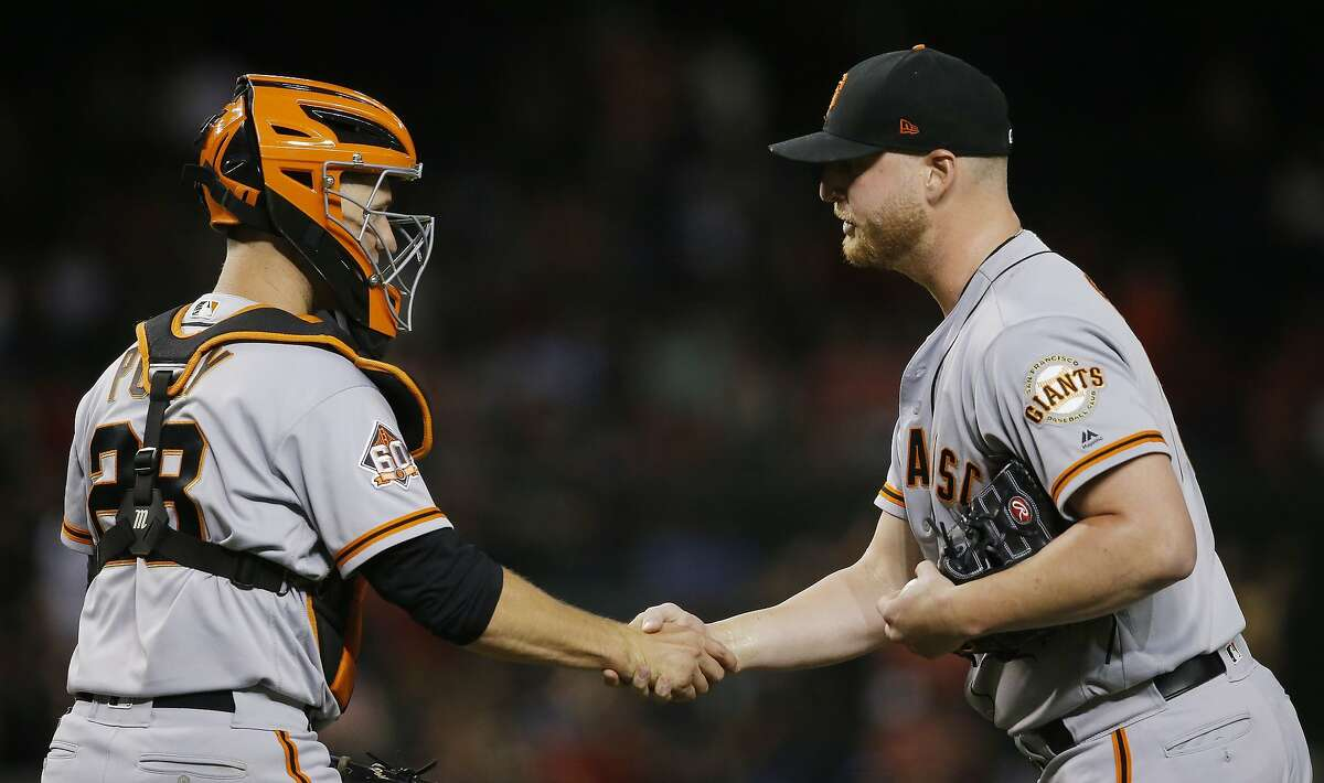 San Francisco Giants relief pitcher Will Smith, right, shakes hands with catcher Buster Posey after the team's 2-1 win in a baseball game against the Arizona Diamondbacks on Friday, June 29, 2018, in Phoenix. (AP Photo/Ross D. Franklin)