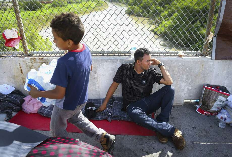 Walter Bindel, from Honduras, sits on the Mexican side of the middle of the Brownsville & Matamoros Express International Bridge for the fourth day in a row hoping for his family to be able to pass together into the United States to seek asylum, Wednesday, June 27, 2018 in Brownsville. Walter, his wife and four children are hoping to escape violence threats against them in their hometown in Honduras. ( Mark Mulligan / Houston Chronicle ) Photo: Mark Mulligan, Houston Chronicle / Houston Chronicle / © 2018 Houston Chronicle