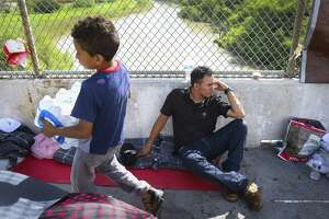 Walter Bindel, from Honduras, sits on the Mexican side of the middle of the Brownsville & Matamoros Express International Bridge for the fourth day in a row hoping for his family to be able to pass together into the United States to seek asylum, Wednesday, June 27, 2018 in Brownsville. Walter, his wife and four children are hoping to escape violence threats against them in their hometown in Honduras. ( Mark Mulligan / Houston Chronicle )