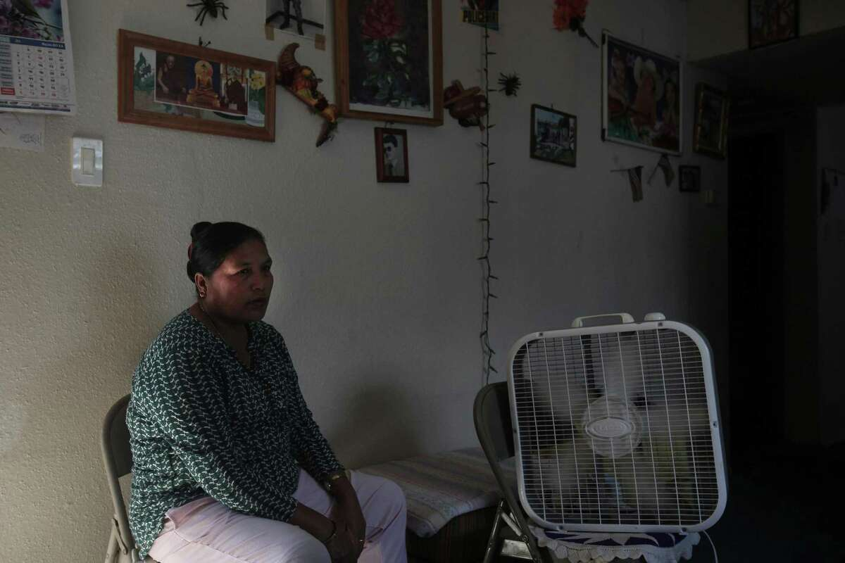 Battle Mya Bhujel sits by a fan with the door open on the second floor of her apartment complex because her air conditioning has been broken for months, along with the lock on their door. She said that even after multiple complains made to the management, they keep saying