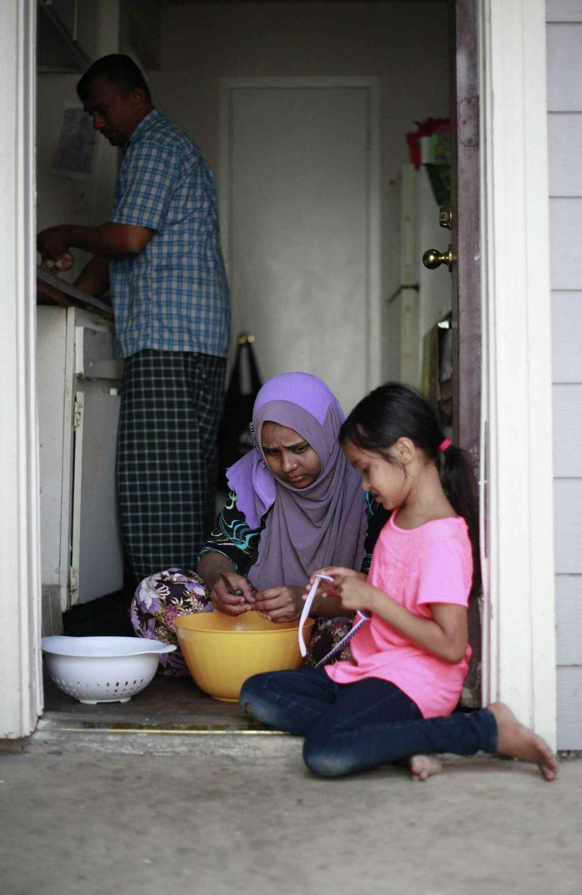 Siti Nur Anisha Binti Mohamad Rashid, 7, shows her mother Saidah Binti Yasin her heart-shaped sunglass as her mother and her father Mohamad Rashid Bin Nurislam prepare dinner.