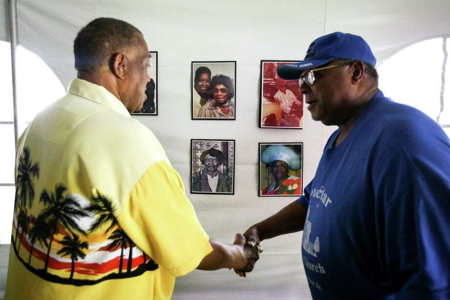 Pastor S.W. Dotson, of Lone Star Missionary Baptist Church, right, greets Frank Moaning, left, as they view the images of deceased Tamina residents who's graves are partially submerged and inaccessible during the Tamina Sweet Rest Cemetery Rally on Saturday, June 30, 2018, at Tamina Community Park. Photo: Michael Minasi, Staff Photographer / Houston Chronicle / © 2018 Houston Chronicle