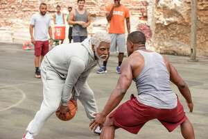 """This image released by Lionsgate shows Boston Celtics basketball player Kyrie Irving, left, portraying Uncle Drew in a scene from the comedy """"Uncle Drew.""""  (Quantrell D. Colbert/Lionsgate via AP)"""