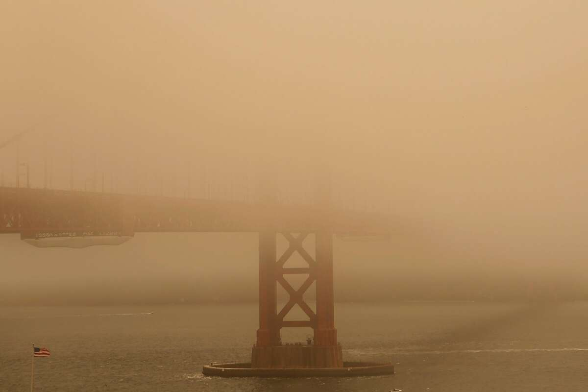An American Flag blows near the Golden Gate Bridge that is consumed in fog and smoke on Sunday, July 1, 2018 in San Francisco, Calif. Air quality in and around San Francisco has been visibly affected by the fires through the weekend.