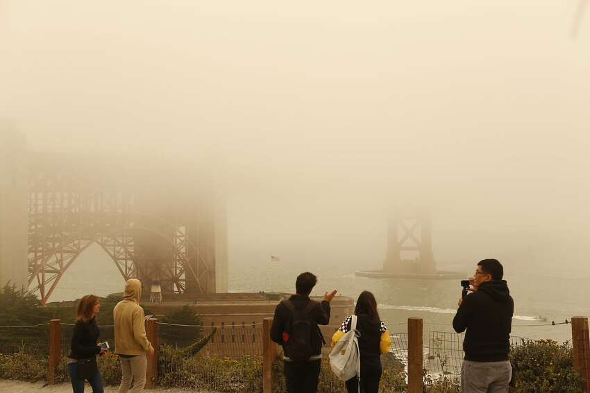 Tourists photograph the Golden Gate Bridge on Sunday, July 1, 2018 in San Francisco, Calif. Air quality in and around San Francisco has been visibly affected by the fires through the weekend.