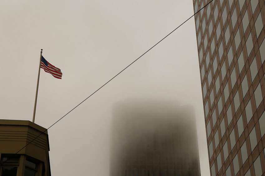 An American Flag blows in the wind around 555 California Street Building that is consumed in haze on Sunday, July 1, 2018 in San Francisco, Calif. Air quality in and around San Francisco has been visibly affected by the fires through the weekend.