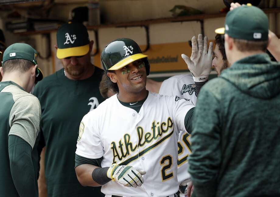 Oakland Athletics' Khris Davis (2) smiles in the dugout after scoring on a double from Matt Olson during the fourth inning of a baseball game against the Cleveland Indians, Sunday, July 1, 2018, in Oakland, Calif. (AP Photo/Marcio Jose Sanchez) Photo: Marcio Jose Sanchez / Associated Press