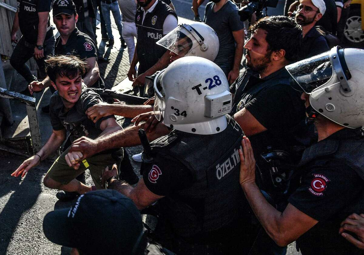 Turkish riot officers beat a gay rights activist after Pride parade organizers refused to recognize a ban by the city of Istanbul.