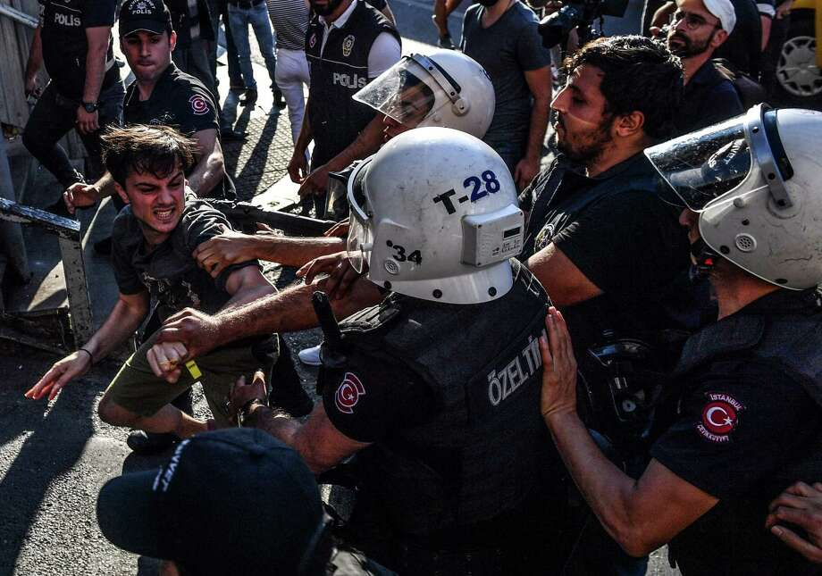 Turkish riot officers beat a gay rights activist after Pride parade organizers refused to recognize a ban by the city of Istanbul. Photo: Bulent Kilic / AFP / Getty Images / AFP or licensors