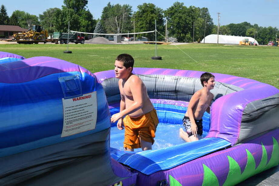 Two unidentified boys play on an inflatable water slide Saturday at Faith Tabernacle Church in Jacksonville. The church celebrated its 60th anniversary with a Summer Fun Fest. There also was a bounce house, dunk tank, food, games and a yard sale. Photo:       Greg Olson | Journal-Courier
