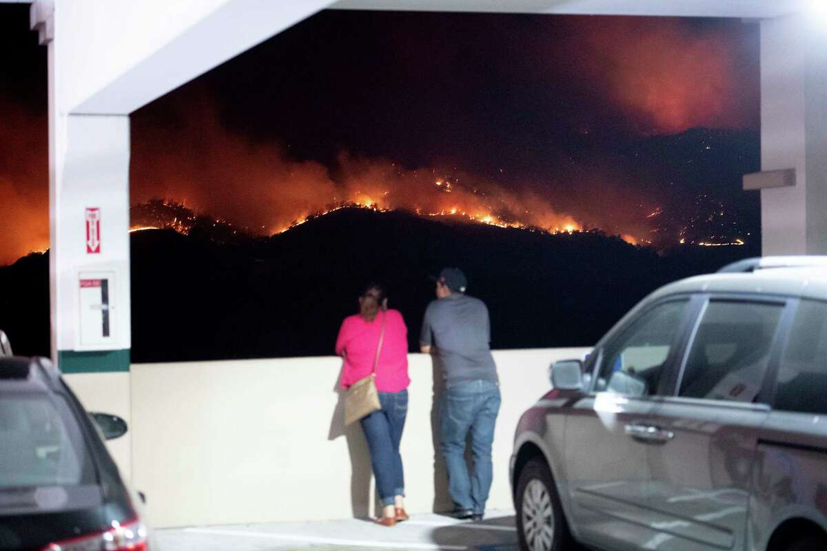 Patrons at Cache Creek Casino Resort watch as a wildfire burns along a ridge top on Sunday, July 1, 2018, in Capay, Calif.