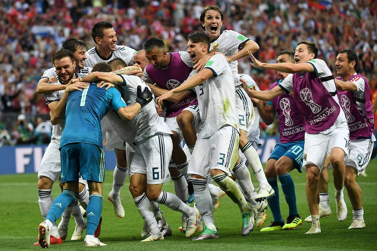 TOPSHOT - Players celebrate Russia's victory at the end of the Russia 2018 World Cup round of 16 football match between Spain and Russia at the Luzhniki Stadium in Moscow on July 1, 2018. / AFP PHOTO / YURI CORTEZ / RESTRICTED TO EDITORIAL USE - NO MOBILE PUSH ALERTS/DOWNLOADSYURI CORTEZ/AFP/Getty Images