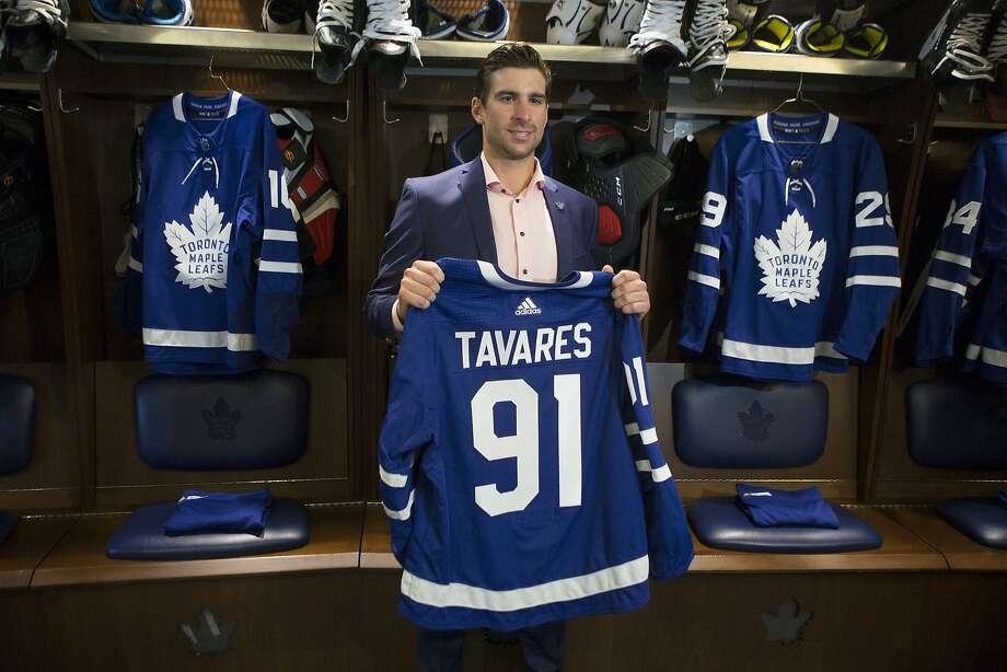 John Tavares holds a Maple Leafs jersey in the locker room following a news conference in Toronto to announce his deal. Photo: Chris Young / Associated Press